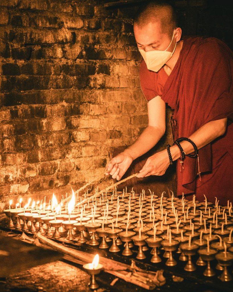 Sherpa monk lighting candles